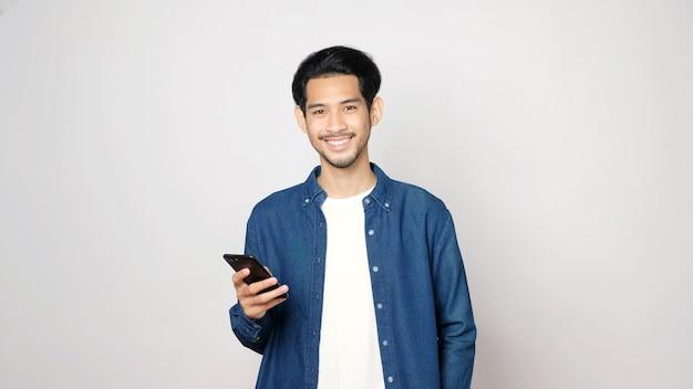 Asiatischer mann, der handy lächelt und kamera betrachtet
