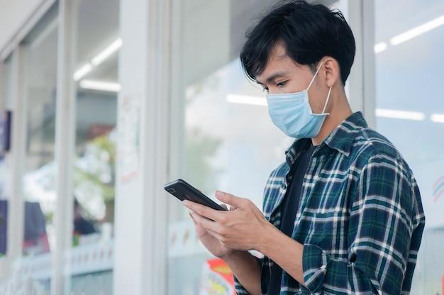 Asiatischer mann, der handy sitzend hält, soziale distanz halten, neue normalität nach covid 19 oder corona-virus