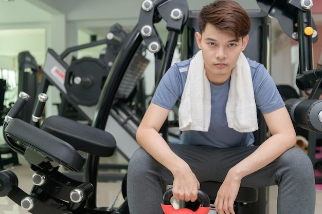 Asiatischer mann, der hanteln im krafttraining anhebt