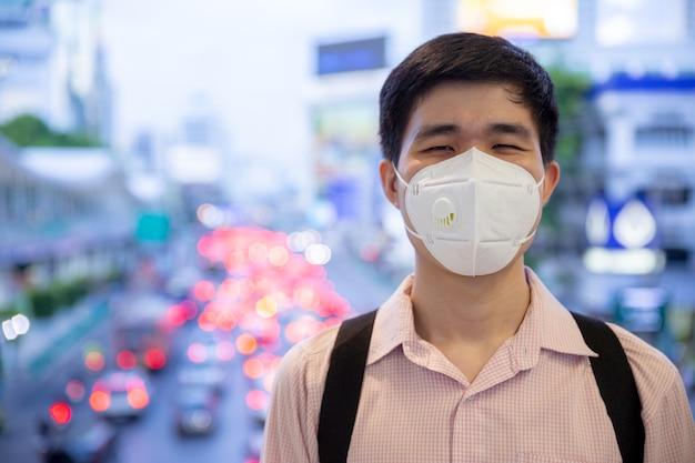 Asiatischer mann, der hinter medizinischer schutzmaske im neuen normalen lebensstilkonzept lächelt.