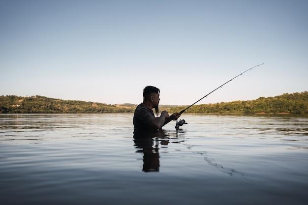 Asiatischer mann, der im fluss bei sonnenuntergang fischt.