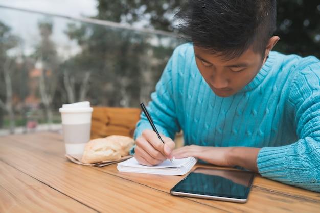Asiatischer mann, der im kaffeestube studiert.