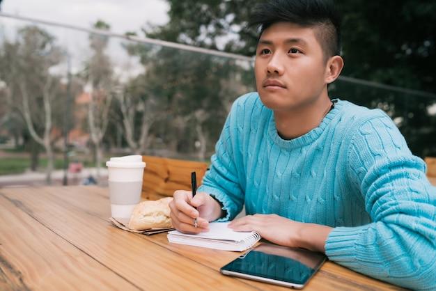 Asiatischer mann, der im kaffeestube studiert