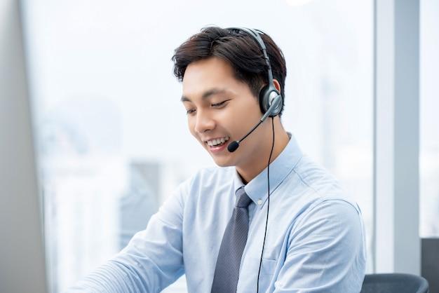Asiatischer mann, der im kundenkontaktcenterbüro arbeitet