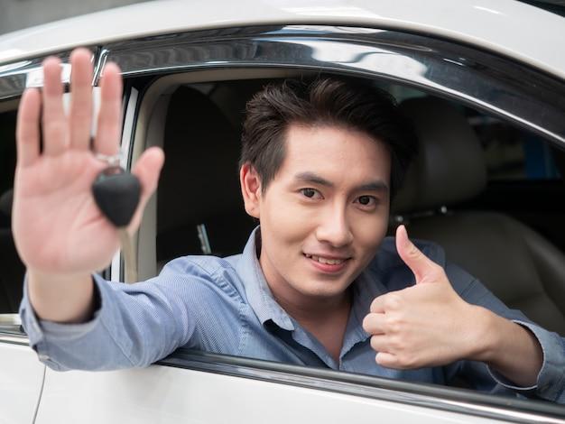 Asiatischer mann, der im neuen auto sitzt und autoschlüssel zeigt. junger attraktiver mann, der salonauto sitzt und offenes fenster schaut.