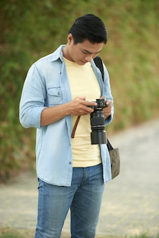 Asiatischer mann, der im park steht und fotos auf kamera überprüft