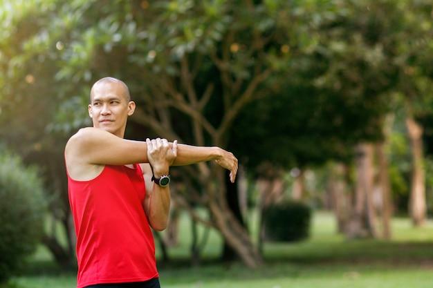 Asiatischer mann, der in den park vor dem laufen am morgen ausdehnt.