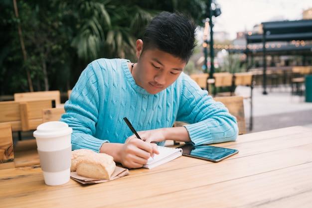 Asiatischer mann, der in der kaffeestube studiert.