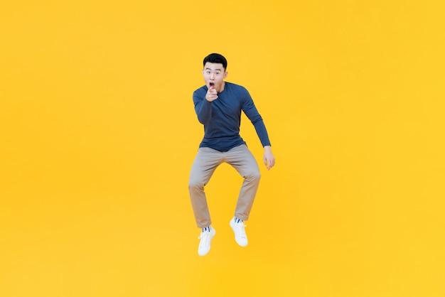 Asiatischer mann, der in der luft springt und zeigt geste