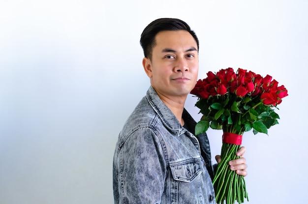 Asiatischer mann, der jeansjacke trägt, die einen blumenstrauß der roten rosen lokalisiert im weißen hintergrund für jubiläums- oder valentinstagkonzept hält.