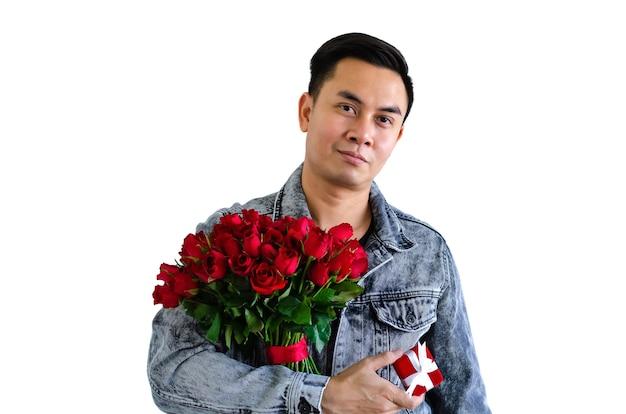 Asiatischer mann, der jeansjacke trägt, die einen blumenstrauß der roten rosen und des roten geschenkkastens lokalisiert im weißen hintergrund für jubiläums- oder valentinstagkonzept hält.