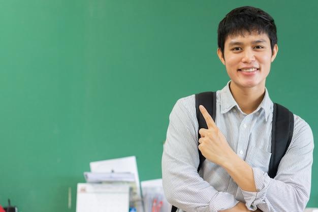 Asiatischer mann der jungen highschool, der mit glücklichem ausdruck lächelt und überreicht grünen tafelhintergrund zeigt