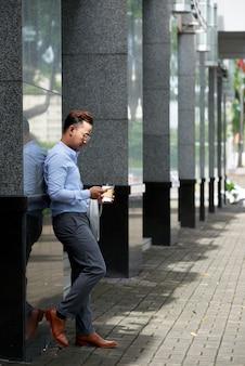 Asiatischer mann, der kaffeepause draußen am bürogebäude hat