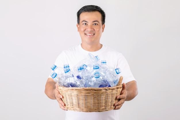 Asiatischer mann, der korb der leeren klaren wasserflaschen hält