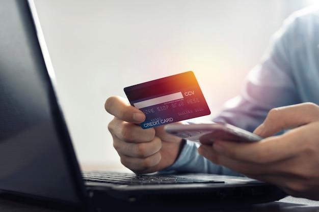 Asiatischer mann, der kreditkarte hält, die online-zahlung nach online-kauf macht