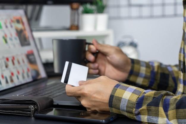 Asiatischer mann, der kreditkarte hält und informationen im internet mit laptop zu hause schreibt