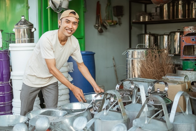 Asiatischer mann, der lächelt, während er die vielen eimer im haushaltsgerätegeschäft anordnet