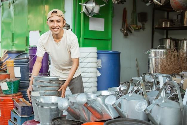 Asiatischer mann, der lächelt, während er ein paar eimer vor dem haushaltsgerätegeschäft anhebt