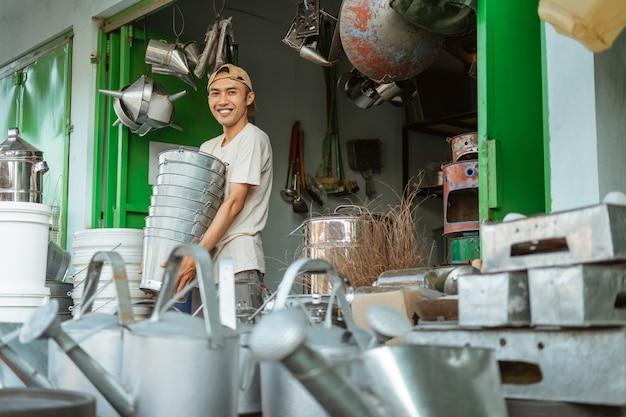 Asiatischer mann, der lächelt, während er viele eimer im haushaltsgerätegeschäft trägt