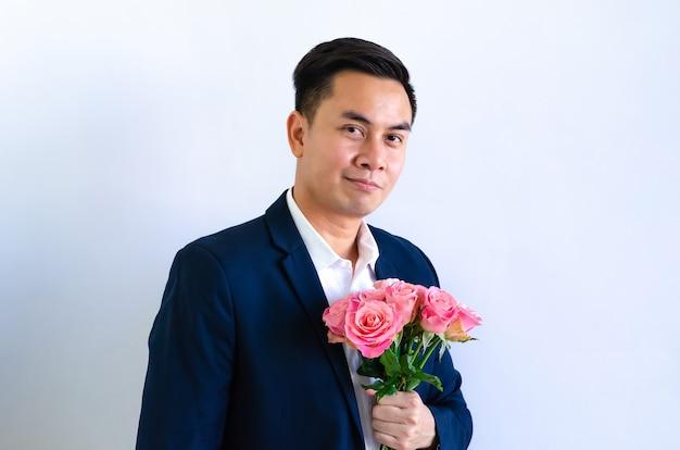 Asiatischer mann, der marineblauanzug hält, der einen blumenstrauß von rosa rosen lokalisiert in weißem hintergrund für jubiläum oder valentinstagkonzept hält.