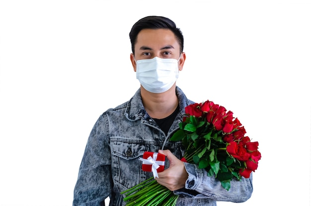 Asiatischer mann, der maske trägt, die rote rosen und geschenkbox für valentinstagkonzept hält.