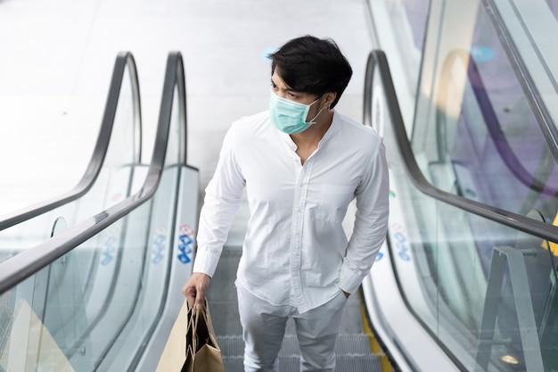 Asiatischer mann, der medizinische gesichtsmaske hält, die einkaufstasche hält