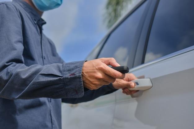 Asiatischer mann, der medizinische maske trägt und schlüssel zum öffnen der autotür hält