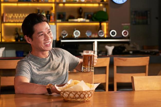 Asiatischer mann, der mit becher bier und imbissen in der kneipe sitzt und weg etwas betrachtet