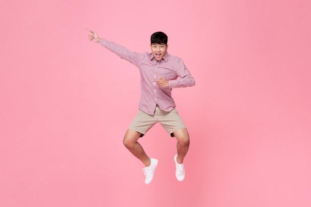 Asiatischer mann, der mit der hand beiseite zeigt springt