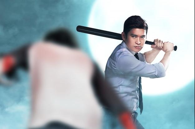 Asiatischer mann, der mit einem baseballschläger auf seiner hand steht, die bereit ist, zombies anzugreifen