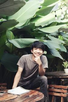 Asiatischer mann, der mit fröhlichem ausdruck im café sitzt