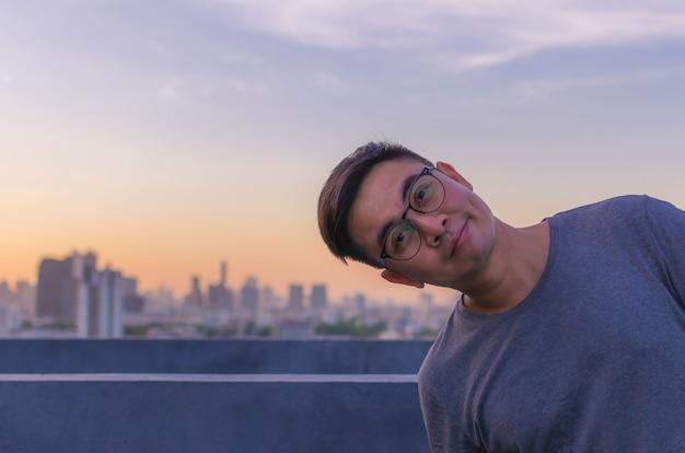 Asiatischer mann, der mit glücklichem gesicht für gutes geistiges gesundheitskonzept lächelt.