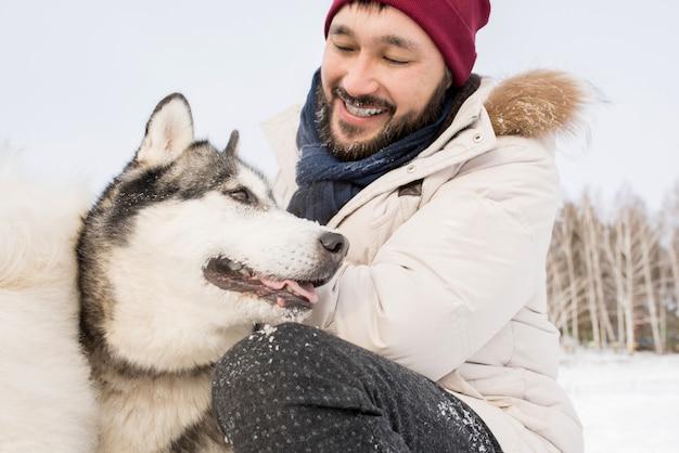 Asiatischer mann, der mit husky-hund spielt