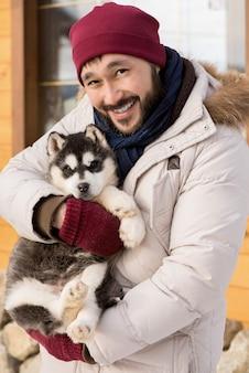 Asiatischer mann, der mit husky pup aufwirft