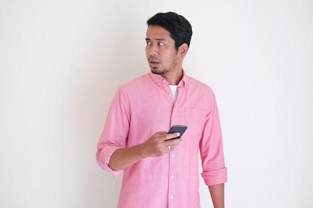 Asiatischer mann, der mit misstrauischem gesichtsausdruck zurückschaut, während er sein handy hält