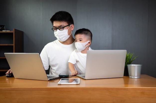 Asiatischer mann, der mit seinem sohn am laptop arbeitet und medizinische schutzmaske trägt