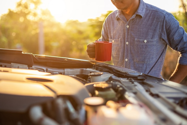 Asiatischer mann, der morgens eine rote kaffeetasse hält und den motor seines autos überprüft
