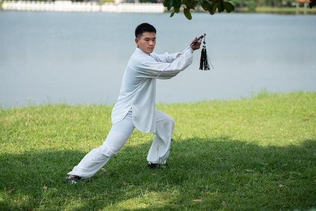Asiatischer mann, der morgens mit tai chi-klinge am park, chinesische kampfkünste, gesunde sorgfalt für lebenkonzept ausarbeitet.