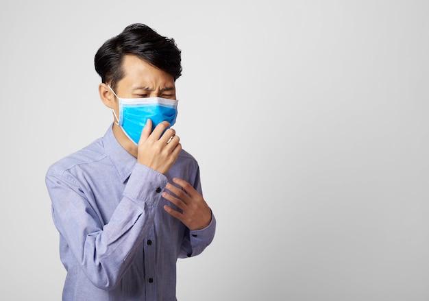 Asiatischer mann, der mund und nase beim husten bedeckt.