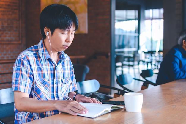 Asiatischer mann, der musik am kaffeehaus hört