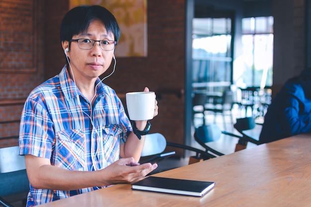 Asiatischer mann, der musik hört und am kaffeehaus liest