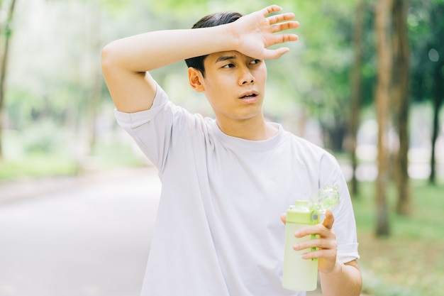 Asiatischer mann, der nach dem joggen im park ruht Premium Fotos