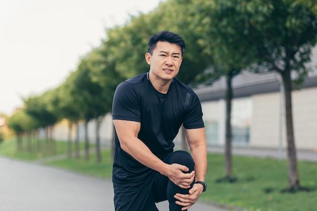 Asiatischer mann, der nach dem laufen und fitness knieschmerzen hält, starke beinschmerzen