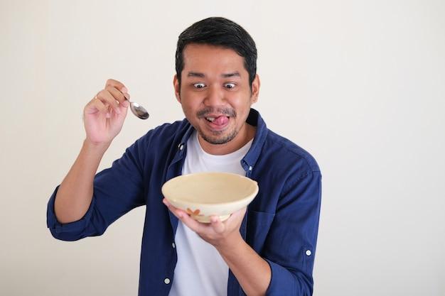 Asiatischer mann, der nach einer leeren essschüssel sucht und einen löffel mit lustigem ausdruck hält