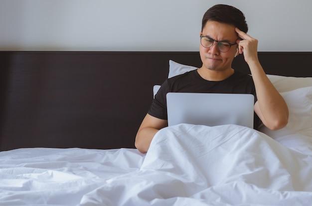 Asiatischer mann, der nachrichten online am laptop beobachtet und sich auf dem bett verwirrend fühlt.
