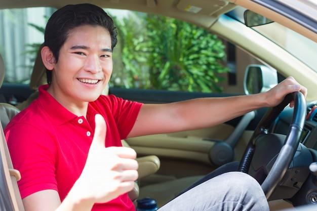 Asiatischer mann, der neues auto fährt
