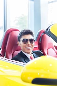 Asiatischer mann, der neues sportauto prüft
