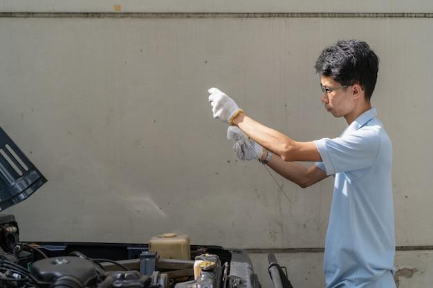 Asiatischer mann, der oben den motorschmierölabschluß überprüft.