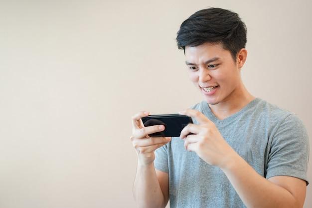 Asiatischer mann, der on-line-spielanwendung mit dem gefühl aufgeregt spielt, entspannen sich zeit