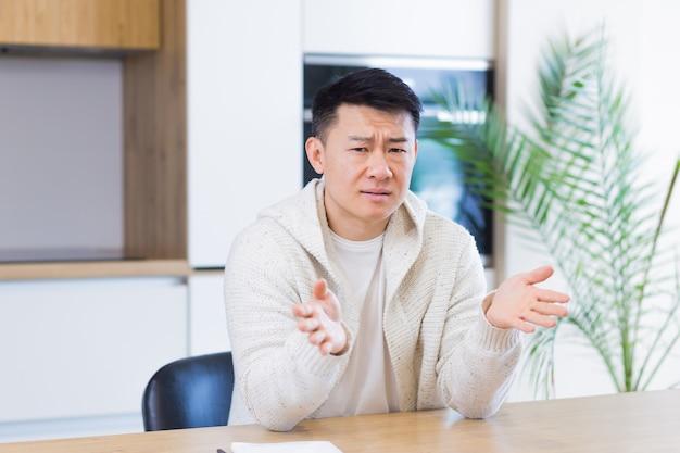Asiatischer mann, der online per videoanruf zu hause im wohnzimmer oder in der küche spricht